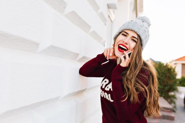 Retrato linda morena com cabelos longos, com chapéu de malha, se divertindo em falar por telefone na rua.