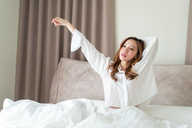 Retrato linda mulher asiática acordar na cama pela manhã
