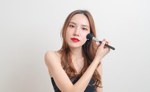 Retrato linda mulher asiática com pincel de maquiagem em fundo branco