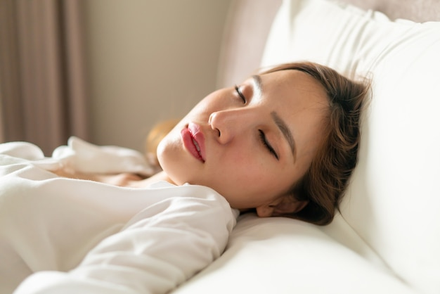 Retrato linda mulher asiática dormindo na cama com travesseiro branco