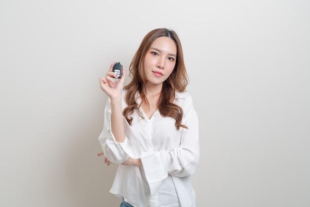 Retrato linda mulher asiática segurando a chave do carro no fundo branco