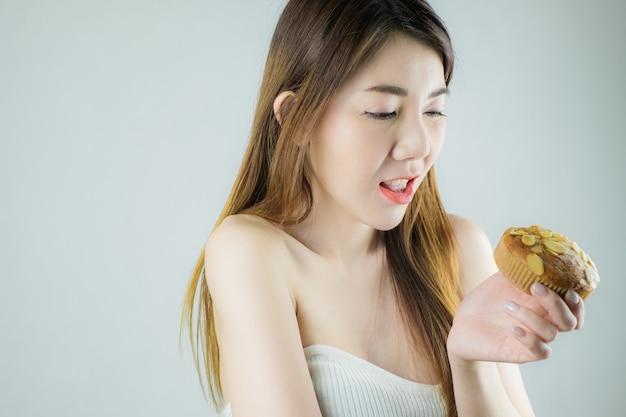 Retrato linda mulher asiática segurando bolinho