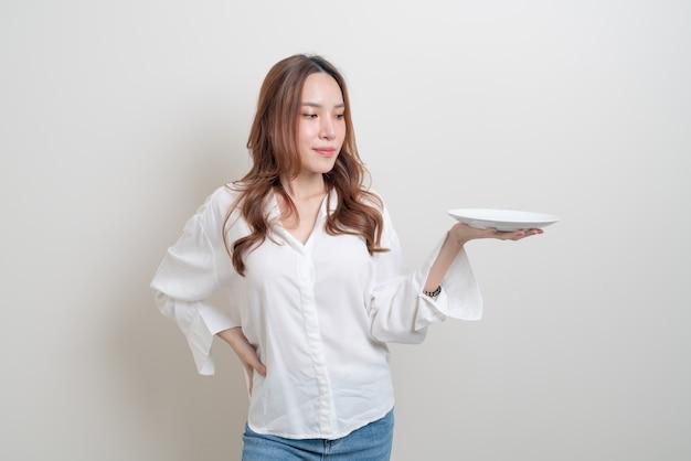 Retrato linda mulher asiática segurando um prato vazio no fundo branco