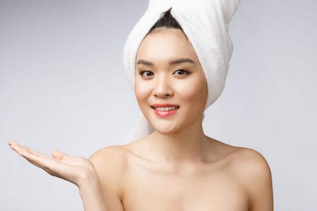 Retrato linda mulher asiática wow surpreendeu e apontando a mão para o lado direito