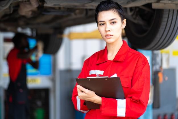 Retrato linda mulher caucasiana mecânica vestindo uniforme vermelho e lista de verificação