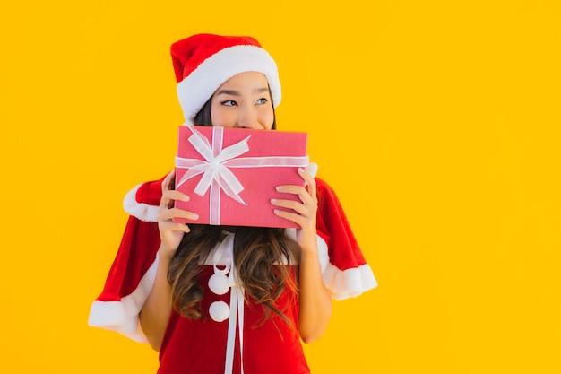Retrato lindo jovem asiático com roupas de natal e chapéu sorrindo feliz com caixa de presente vermelha