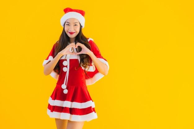 Retrato lindo jovem asiático com roupas de natal e chapéu sorrindo feliz com o coração