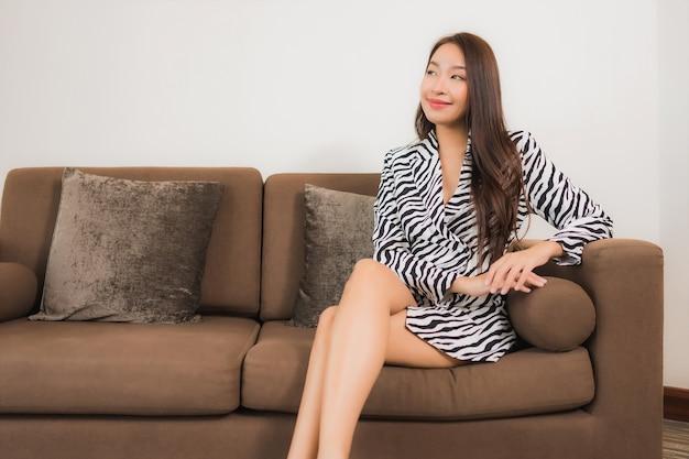 Retrato lindo jovem asiático sorrindo relaxado no sofá no interior da sala de estar