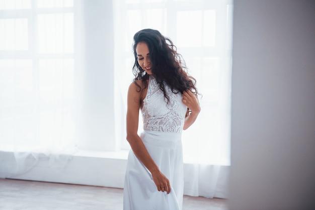 Retrato lindo. mulher bonita de vestido branco fica na sala branca com luz do dia através das janelas