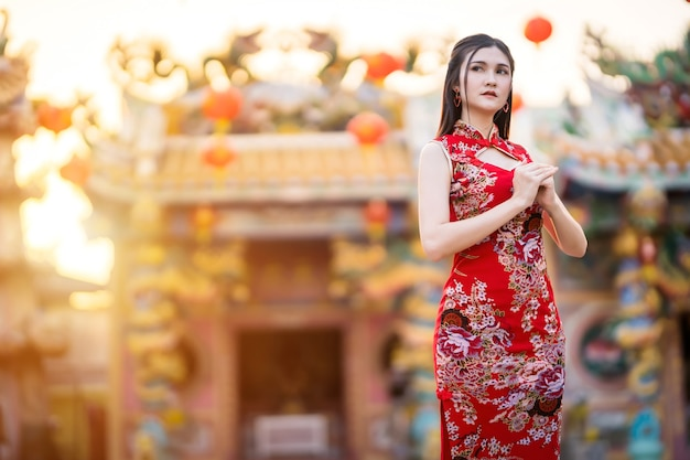 Retrato lindo sorrindo jovem asiática vestindo um cheongsam chinês tradicional vermelho, para o festival de ano novo chinês no santuário chinês