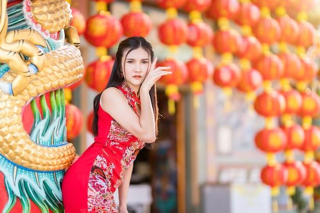 Retrato lindo sorrindo jovem asiática vestindo um cheongsam chinês tradicional vermelho