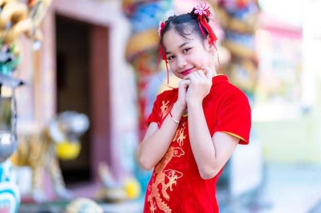 Retrato lindo sorrisos menina asiática bonitinha usando cheongsam chinês tradicional vermelho, para o festival de ano novo chinês no santuário chinês