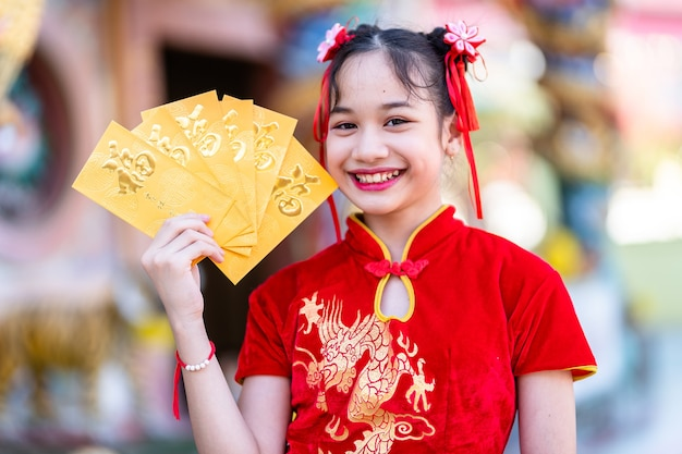 Retrato lindo sorrisos menina asiática bonitinha vestindo cheongsam chinês tradicional vermelho, segurando envelopes amarelos para o festival de ano novo chinês no santuário chinês