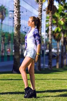 Retrato louco e feliz de mulher fazendo caretas, aproveite seus dias quentes de verão de fim de semana, roupas da moda hipster brilhante, coloque as mãos para o ar e relaxe, país exótico.