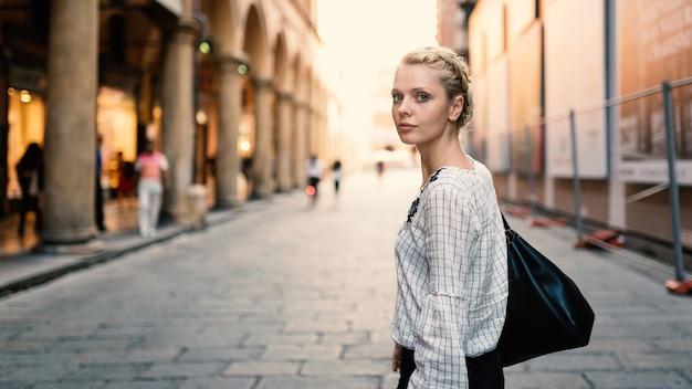 Retrato louro bonito novo do estilo de vida da mulher ao ar livre na bolonha, italy. clarão natual