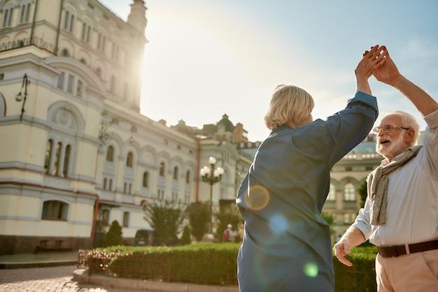 Retrato lúdico de um lindo casal sênior dançando juntos ao ar livre em um dia ensolarado