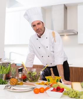 Retrato masculino do chef na bancada branca na cozinha
