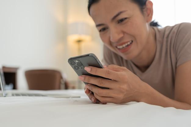 Retrato matinal de uma mulher asiática bonita sorridente usando um smartphone