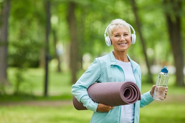Retrato médio de mulher caucasiana madura e alegre usando fones de ouvido brancos, segurando um tapete de ioga e uma garrafa de água, sorrindo para a câmera