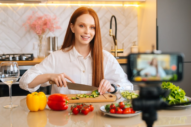 Retrato médio de uma atraente ruiva vlogger gravando um vídeo-blog de culinária sobre culinária em