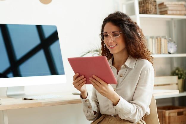 Retrato médio horizontal de uma jovem empresária usando óculos e computador tablet para trabalhar