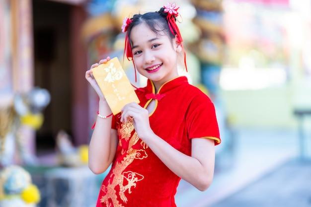 Retrato menina asiática bonitinha usando cheongsam vermelho tradicional chinês, segurando envelopes amarelos com o texto em chinês