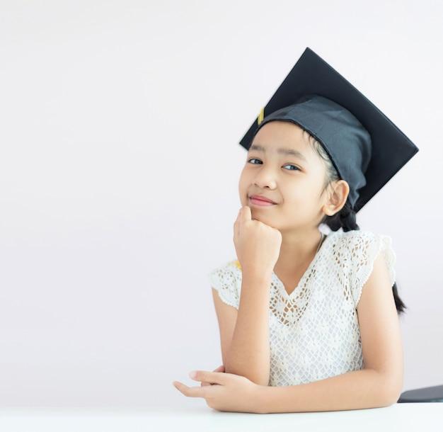 Retrato menina asiática está usando chapéu de pós-graduação e sorrir com felicidade