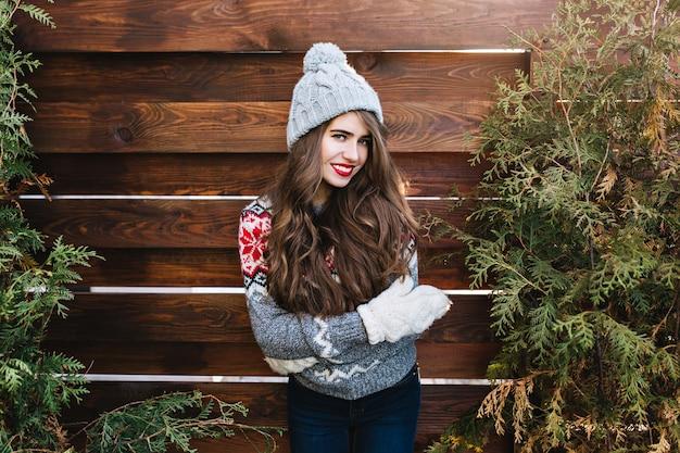 Retrato menina bonita com cabelo comprido em roupas de inverno e luvas quentes na madeira. ela está sorrindo .