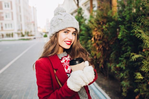Retrato menina bonita morena com cabelos longos, com casaco vermelho, andando na rua. ela segura o café para viagem com luvas brancas, sorrindo.