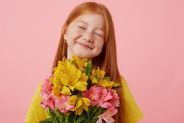 Retrato menina ruiva petite sardas com duas caudas, amplamente sorridente e parece fofa, com os olhos fechados, segura o buquê, usa uma camiseta amarela, fica sobre fundo rosa.