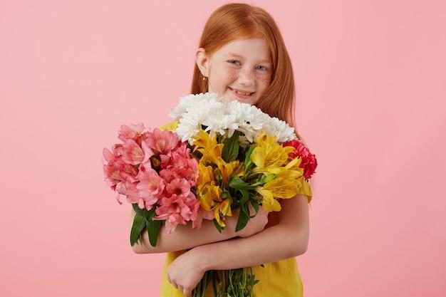 Retrato menina ruiva petite sardas com duas caudas, amplamente sorridente e parece fofa, usa uma camiseta amarela, segura o buquê e fica sobre um fundo rosa.