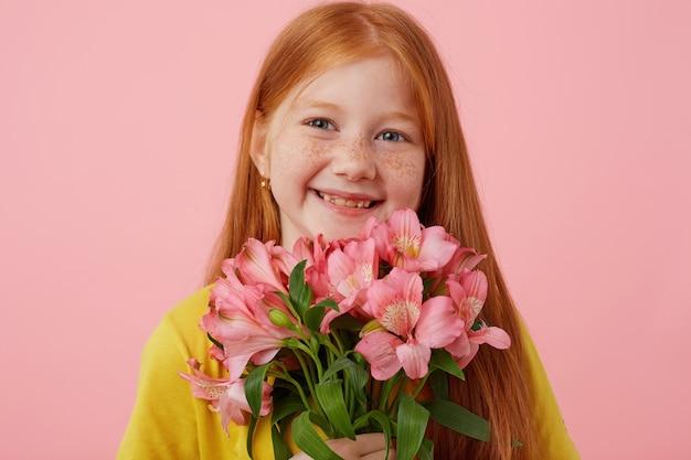 Retrato menina ruiva petite sardas com duas caudas, amplamente sorrindo e parece fofo, segura o buquê, usa uma camiseta amarela, fica sobre um fundo rosa.