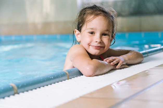Retrato menina se divertindo na piscina interior. a menina está descansando no parque aquático.