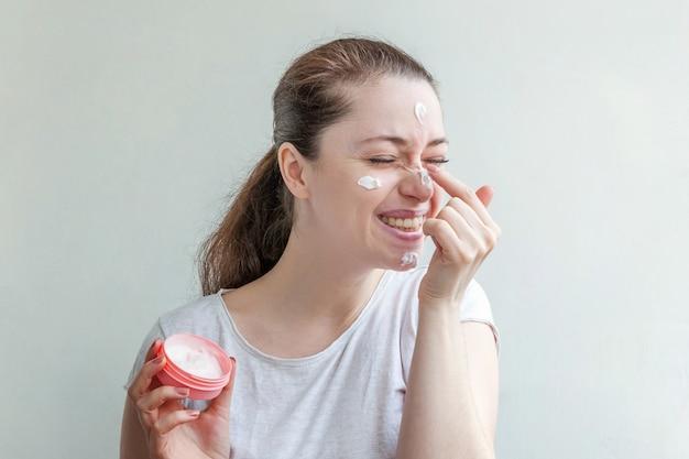 Retrato mínimo da beleza retrato da menina da jovem mulher que aplica a máscara ou a nata nutritiva branca na cara isolada na parede branca. conceito de spa cosmético orgânico de limpeza eco skincare.