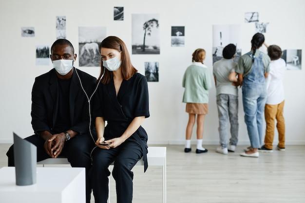 Retrato mínimo de casal mestiço na galeria de arte usando máscaras e ouvindo guia de áudio, copie o espaço
