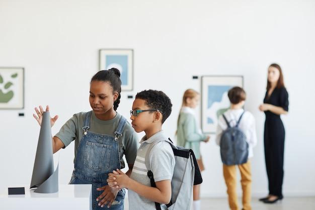Retrato mínimo de crianças em idade escolar visitando a galeria de arte e olhando esculturas modernas, copie o espaço