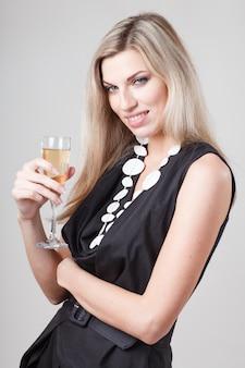 Retrato modelo bonito sobre o fundo branco do estúdio segura o copo de vinho