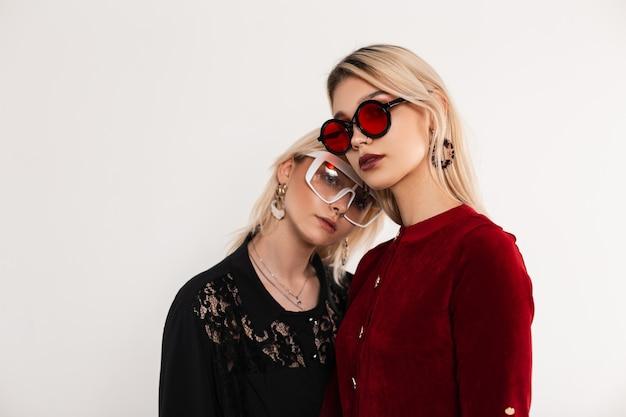 Retrato moderno de duas adolescentes com óculos coloridos e cabelos loiros em vestidos vermelho-escuros em pé perto de uma parede cinza vintage