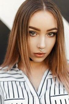 Retrato moderno de uma bela jovem com brincos no nariz e uma blusa listrada