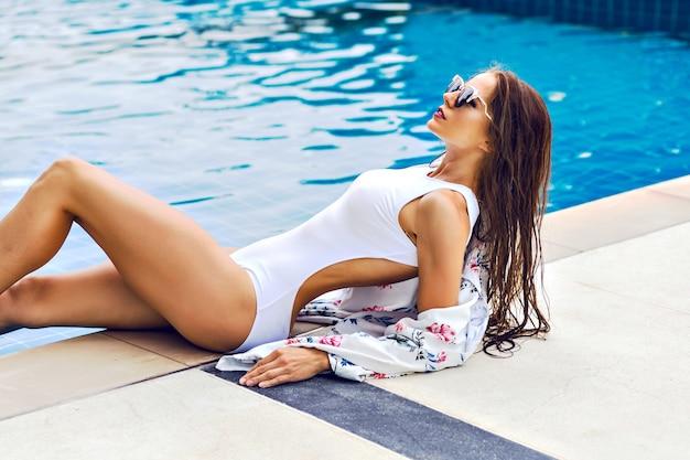 Retrato moderno de verão de mulher esportiva deslumbrante relaxada perto da piscina em hotel de luxo
