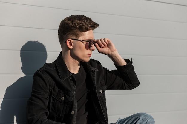 Retrato moderno na moda jovem em elegante jaqueta jeans preta com óculos de sol da moda