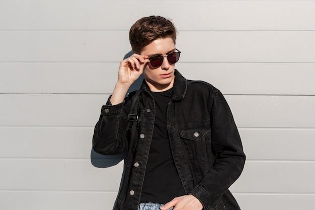 Retrato moderno na moda jovem em jaqueta jeans preta elegante com óculos de sol vintage