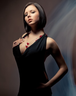 Retrato monocromático da charada linda garota esbelta em um vestido preto em um fundo preto no estúdio. conceito de feminilidade, beleza e cuidado. lugar para anunciar