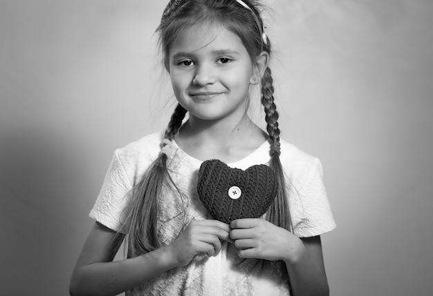 Retrato monocromático de uma linda garota sorridente segurando um coração decorativo no peito