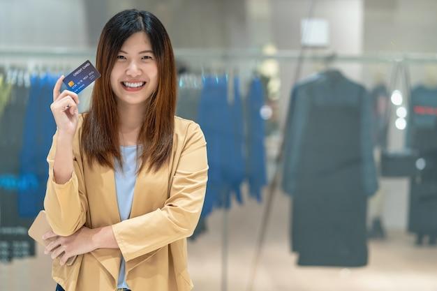Retrato, mulher asian, usando, cartão crédito, com, esperto, telefone móvel, para, shopping online, em, departamento