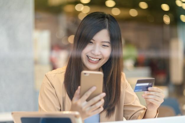 Retrato, mulher asian, usando, cartão crédito, com, esperto, telefone móvel, para, shopping online, em, loja