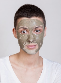 Retrato mulher bonita com tratamento de lama no rosto