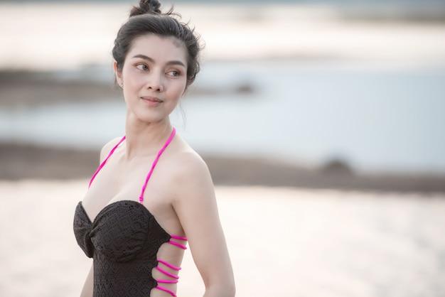 Retrato mulher bonita em trajes de banho com um maiô de uma peça lindo corpo esportivo caminhando e posando em uma praia