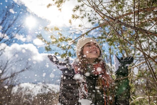 Retrato mulher bonita jovem curtindo e brincando com neve no inverno