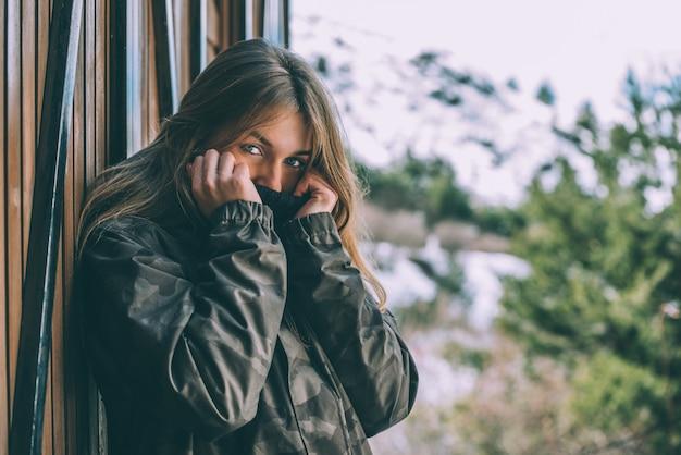 Retrato mulher bonita jovem no inverno em uma cabana na neve
